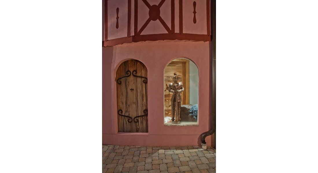 A silver knight stands holding his sword upright in a window beside a wooden door on this unique pink house