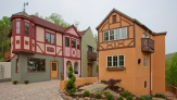 A pink and Orange bavarian style house with red trim dit quaintly side- by- side