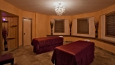 two red massage tables in an a natural orange octagonal room