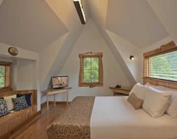Cozy room with light blue walls and steep sloped roof. One queen bed and build-in bench with many soft pillows.