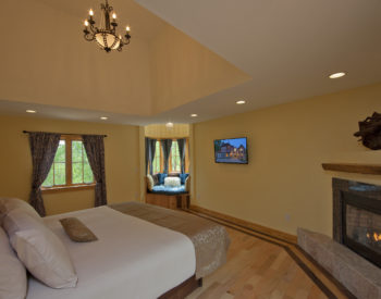 Beautiful room with light yellow walls and king size bed with cream sheets and walnut bed frame and headboard.