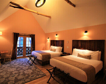 Large room with hardwood floors and two queen size beds made from walnut.