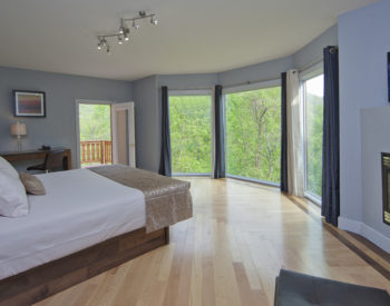 Light shines through the huge windows across the hard wood floors onto the beautifully made white bed