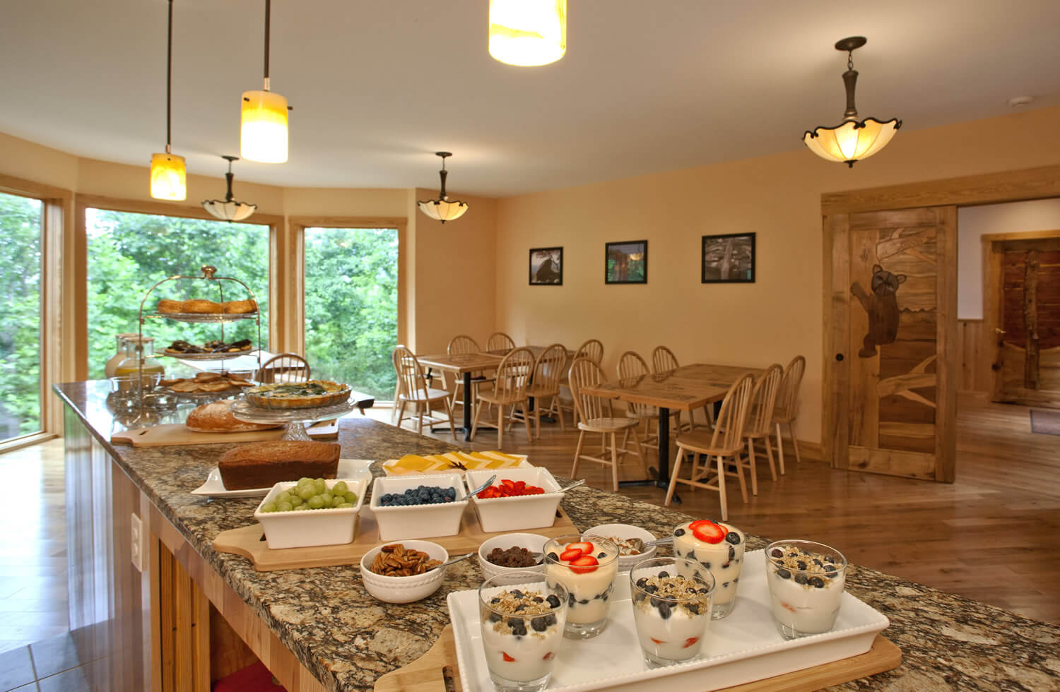 Delicious yogurt parfaits and other fruit and goodies rest on the buffet in this warm yellow dining room