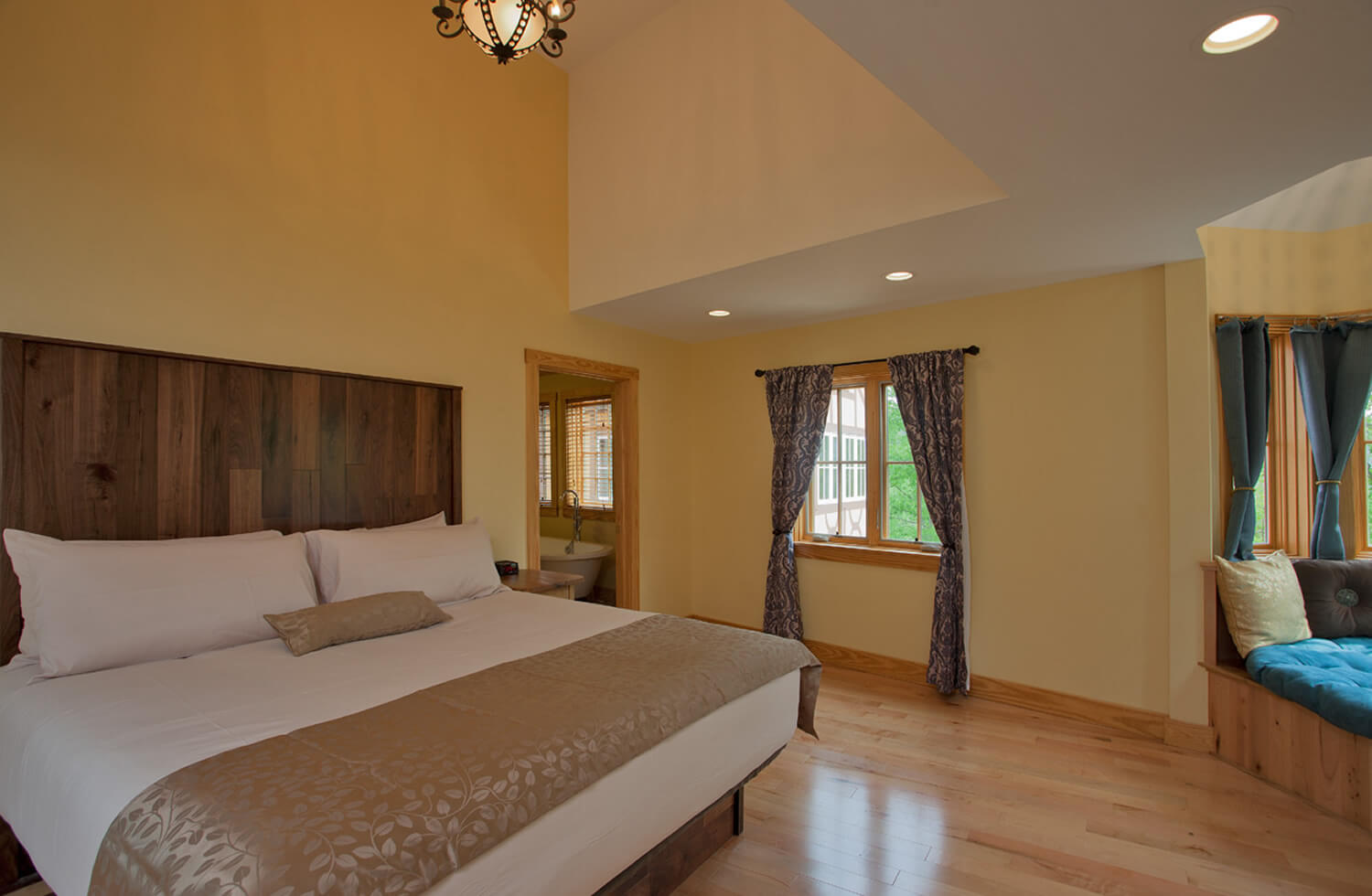 A yellow guestroom has white accented on unique ceiling; a huge well-made white bed with tan accent pillow and throw