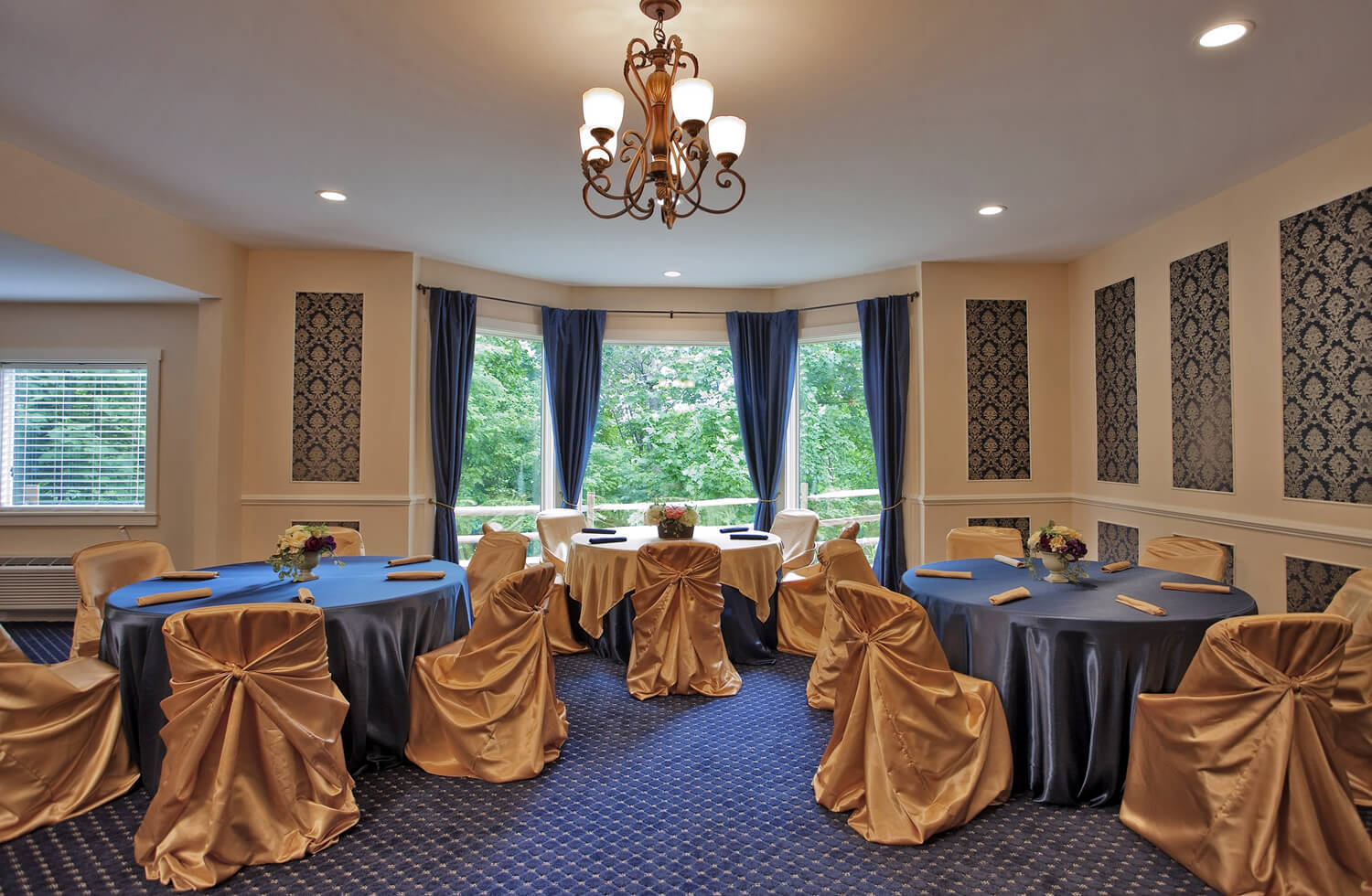 Large meeting room with classic look. Blue and gold tones in a wall paper and carpet. Large champagne chandelier in a middle of a tall ceiling. Three round tables decorated in satin blue and gold table cloth and napkins.