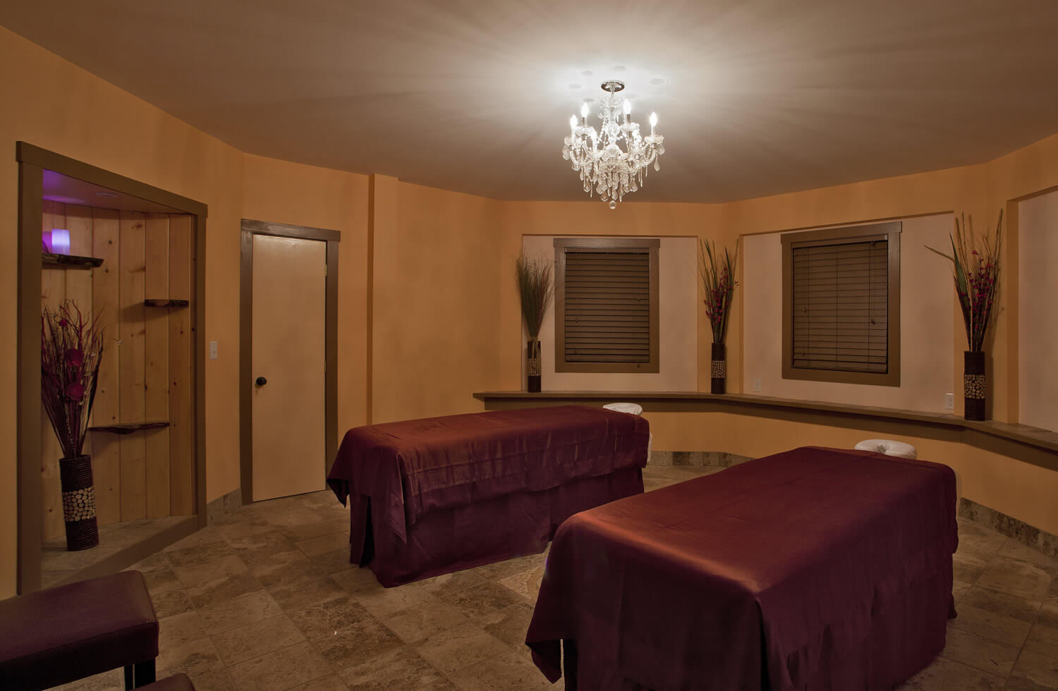octagonal room with large windows and chandelier. Two massage tables with burgundy satin sheets in the middle of the room.