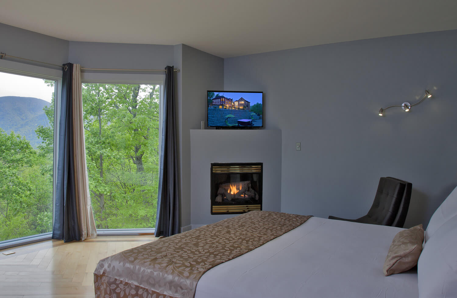 A white bed with gold accents and throw rests across from a fireplace and open window with mountain view